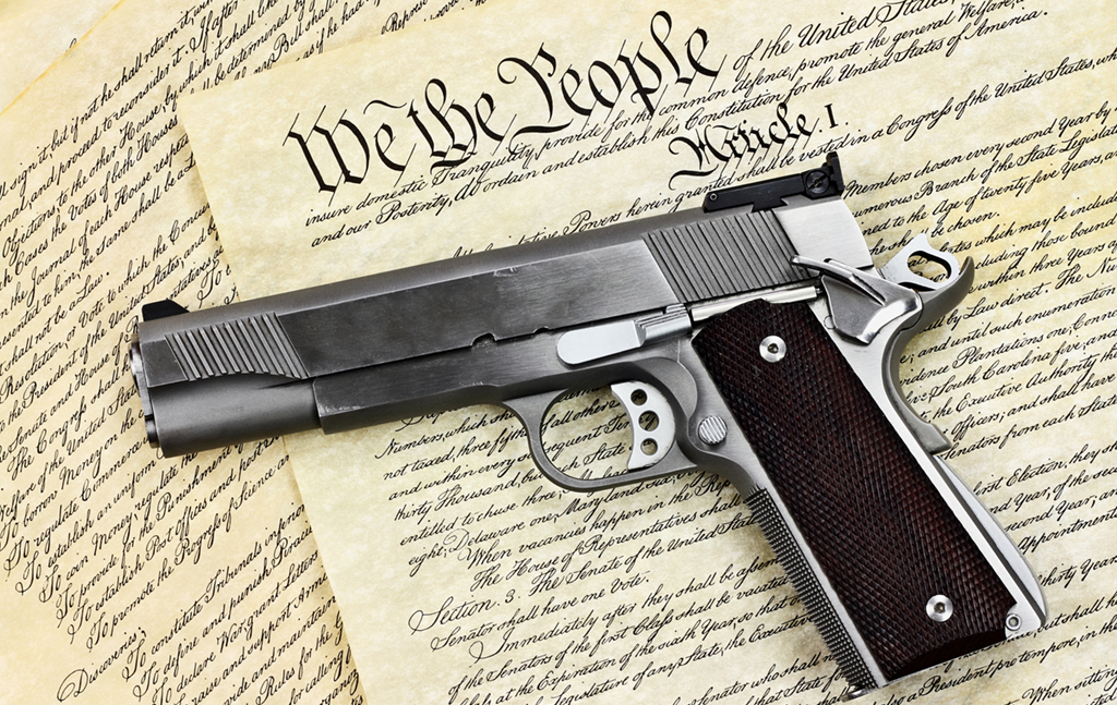 image of a fire arm laying on a copy of the constitution